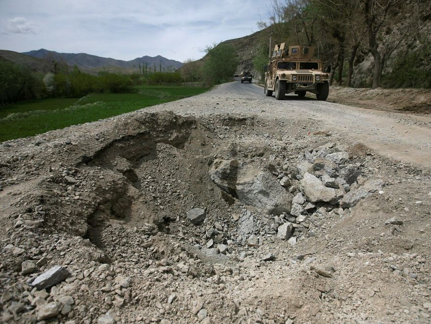 ** FILE ** A U.S. Humvee of the 3rd Brigade, 10th Mountain Division, drives near a crater caused by a roadside bomb attack on a U.S. vehicle in Tangi Valley in Wardak province, west of Kabul, Afghanistan, in 2009.