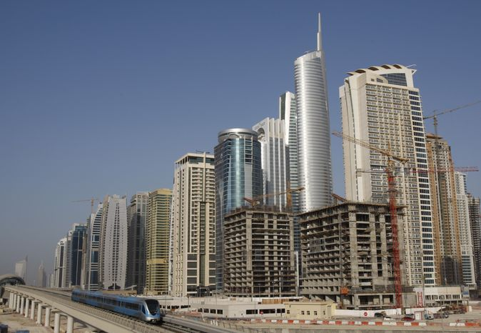 ** FILE ** This Sept. 13, 2009, photo shows a metro train passing the Jumairah Lake towers district in Dubai