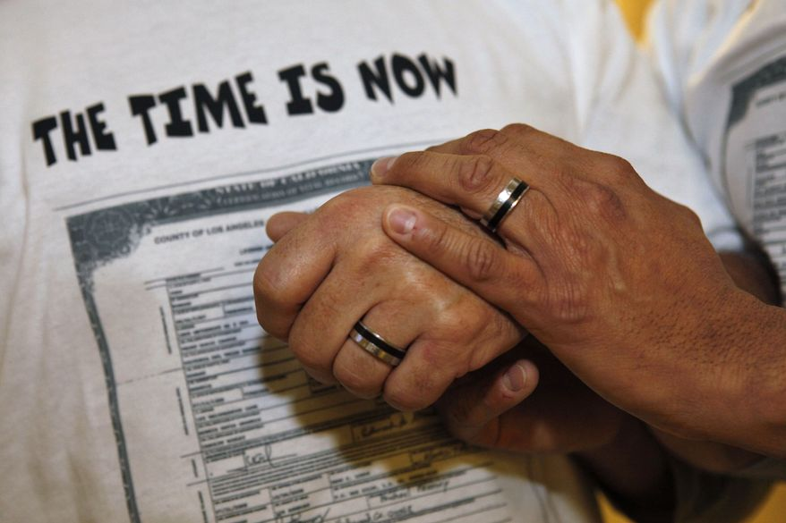 ** FILE ** In this Oct. 6, 2009, file photo, Ed Grandis, left, and Juan D. Rondon, hold hands after a bill allowing same-sex marriage in the District of Columbia was introduced at a City Council meeting in Washington. (AP Photo/Jacquelyn Martin, File)