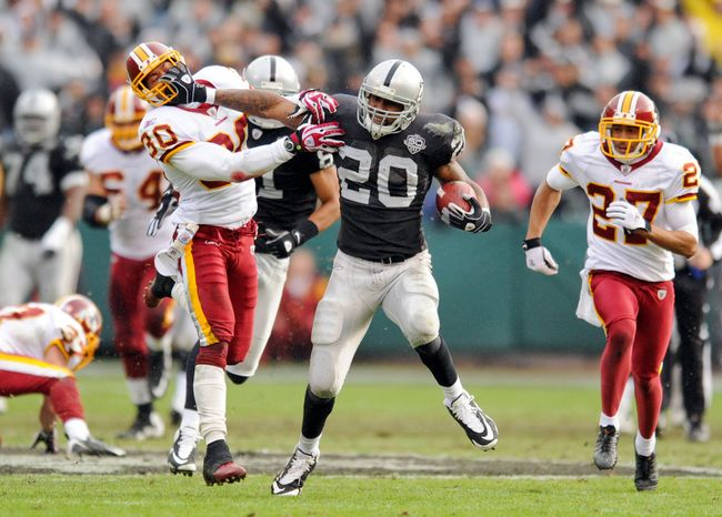 Redskins LaRon Landry (30) can't stop Raiders Darren McFadden (20) from picking up 48 yards in the first quarter. (Michael Connor / The Washington Times)