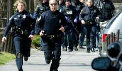 ** FILE ** Police officers run from Norris Hall on the Virginia Tech campus in Blacksburg, Va., on April 16, 2007, after the worst mass shooting in modern U.S. history. (AP Photo)