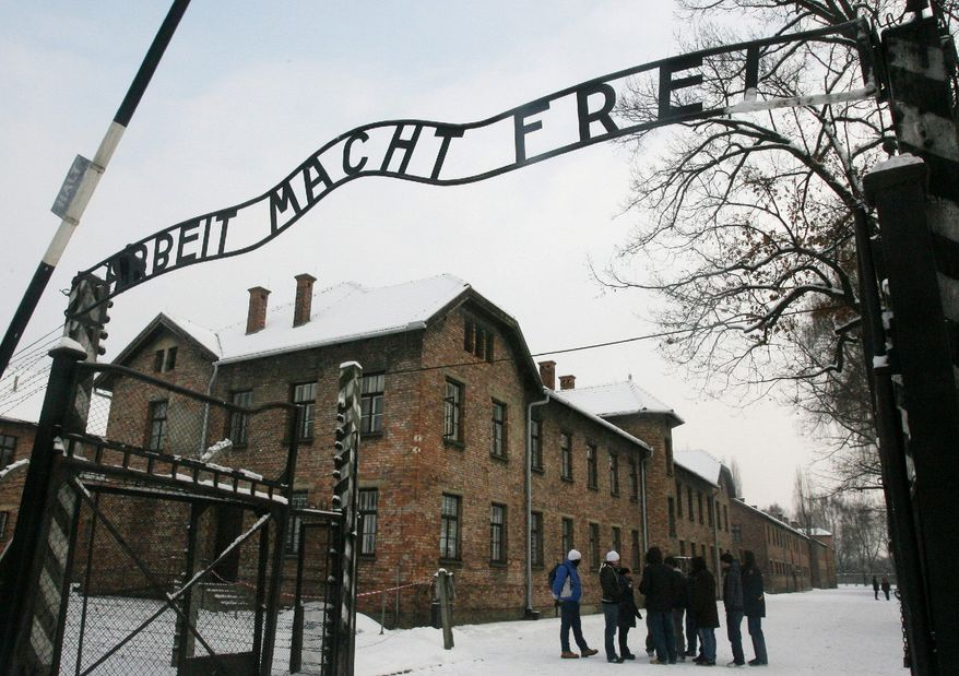 "ASSOCIATED PRESS PHOTOGRAPHS Tourists pause near the former Nazi death camp Auschwitz-Birkenau in Oswiecim, Poland, where the infamous iron sign reading ""Work Sets You Free"" was stolen before dawn on Friday."