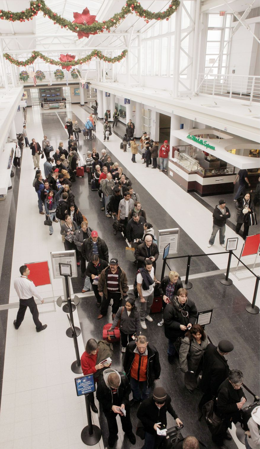 ** FILE ** Passengers at Chicago's O'Hare International Airport prepare to go through security in December 2009.