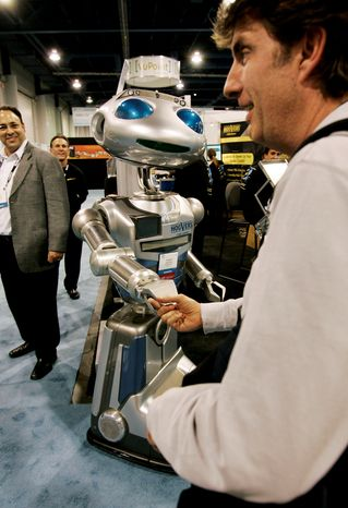 ** FILE ** An attendee shakes hands with Hoovers Mobile's remote-controlled Robot Hoovie at the International Consumer