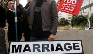 Luke Otterstad carries a sign about traditional marriage as demonstrators protest around him during a rally in front of a federal courthouse in San Francisco, Monday, Jan. 11, 2010. (AP Photo/Paul Sakuma)