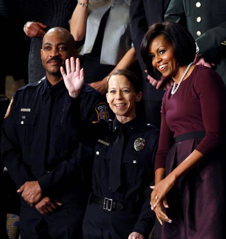 First lady Michelle Obama stands with Kimberly Munley of Killeen, Texas, and Mark Todd of Killeen, Texas, on Capitol Hill in Washington, Wednesday, Jan. 27, 2010, prior to the start of President Barack Obama's State of the Union address. (AP Photo/Charles Dharapak)