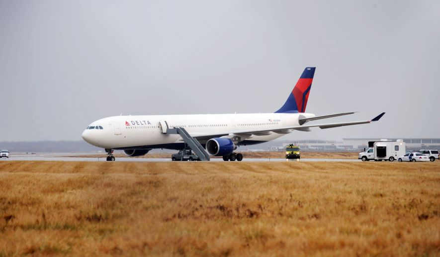 **FILE** Passengers on Northwest Airlines Flight 253 were evacuated after arriving at Detroit Metropolitan Airport from Amsterdam on Christmas Day in 2009. Officials accused a Nigerian aboard, identified as Umar Farouk Abdulmutallab, of trying to ignite an explosive device in his underwear. Northwest merged with Delta Air Lines in 2008. (Associated Press)