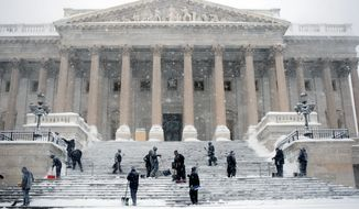 BLOOMBERG NEWS SNOW DAY: Workers shovel snow off the steps of the U.S. Capitol building in the District on Wednesday. A second blizzard in a week pounded the region creating near-whiteout conditions that dumped record levels of snow at area airports.