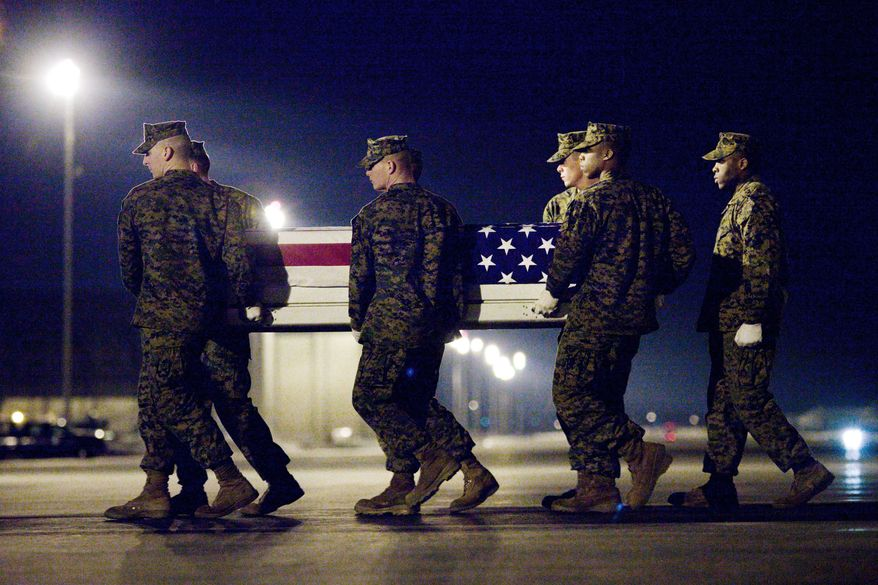 A Marine team carries a transfer case containing the remains of Marine Lance Cpl. Joshua H. Birchfield at Dover Air Force Base in Delaware on Sunday. According to the Department of Defense, Cpl. Birchfield, of LaPorte, Ind., died while supporting Operation Enduring Freedom. (Associated Press)