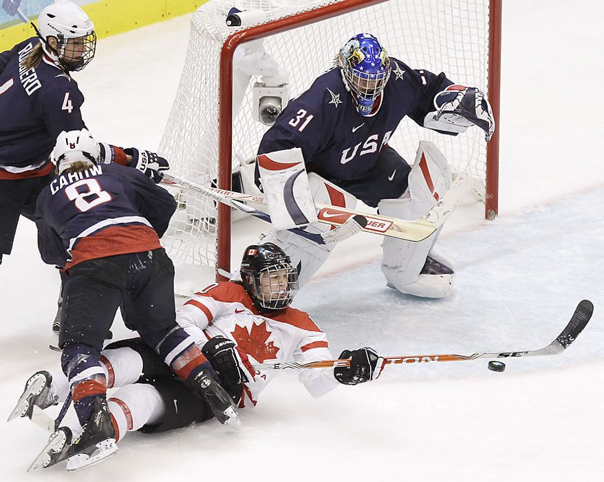 Canada's forward Gillian Apps (10) falls as she tries to shoot on USA's goalie Jessie Vetter in the second period of the women's gold medal ice hockey game at the Vancouver 2010 Olympics in Vancouver, British Columbia, Thursday, Feb. 25, 2010. Also defending for USA are Caitlin Cahow (8) and  Angela Ruggiero (4). (AP Photo/Julie Jacobson)