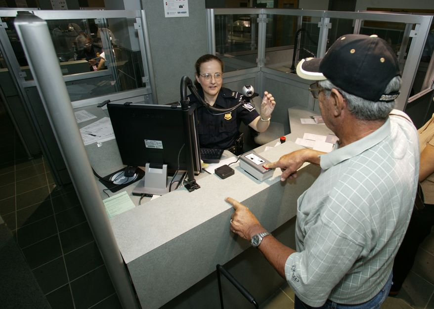 **FILE** A Customs and Border Protection officer takes a passenger's fingerprints upon arrival in Washington. (Department of Homeland Security)