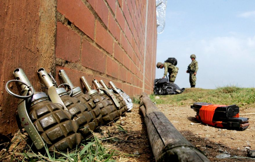 **FILE** Grenades allegedly belonging to soldiers who were killed by rebels sit on the ground in Corinto in southern Colombia in November. (Associated Press)