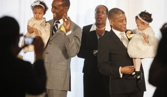 Rocky Galloway (left) and Reginald Stanley hold their twin daughters after the two men were married by the Rev. Sylvia E. Sumter (center) on Tuesday, March 9, 2010, the first day that gay marriage was legal in Washington. (AP Photo/Jacquelyn Martin)
