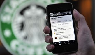 The Foursquare application is shown on an iPhone in front of a Starbucks in San Francisco on Nov. 20, 2009. (Associated Press) **FILE**
