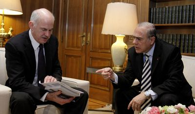 Former Greek Prime Minister George Papandreou (left) talks with Angel Gurria, secretary-general of the Organization for Economic Cooperation and Development (OECD), during a meeting in Athens on Monday, March 15, 2010.  (AP Photo/Petros Giannakouris) **FILE**