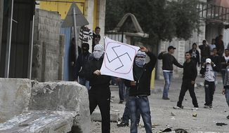 Palestinians hold up a banner with a swastika during clashes with Israeli soldiers, not pictured, near the Kalandia checkpoint between the West Bank city of Ramallah and Jerusalem, Friday, March 19, 2010. (AP Photo/Tara Todras-Whitehill) ** FILE **