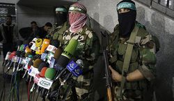 Abu Obeida, center, spokesman for the Qassam Brigades, the Hamas' military wing, holds a press conference in Gaza City, Friday, March 26, 2010. Two Israeli soldiers were killed during a gunbattle with Gaza militants that widened into some of the fiercest fighting in the territory since Israel's January 2009 war. Four militants died in that clash and in another exchange of fire nearby. (AP Photo/Hatem Moussa)