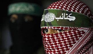 ** FILE ** Abu Obeida, center, spokesman for the Qassam Brigades, the Hamas' military wing, holds a press conference in Gaza City, Friday, March 26, 2010. (AP Photo/Hatem Moussa)