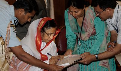 Indian President Pratibha Patil (second left) puts her signature after being enumerated for the national census, at the presidential palace in New Delhi, India, Thursday, April 1, 2010. India kicked off the national census of its billion-plus population with a 2.5 million strong army of census-takers fanning out across the country to conduct what has been billed the world's largest administrative exercise. (AP Photo/Manish Swarup)