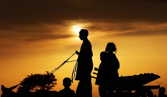 A Pakistani youth rides a donkey cart loaded with other children, as the sun sets on the outskirts of Islamabad, Pakistan, Friday, April 2, 2010. (AP Photo/Muhammed Muheisen)
