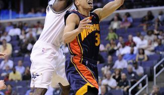 Golden State Warriors guard Stephen Curry, right, goes to the basket against Washington Wizards guard Cedric Jackson during the first half of an NBA basketball game, Tuesday, April 6, 2010, in Washington. (AP Photo/Nick Wass)