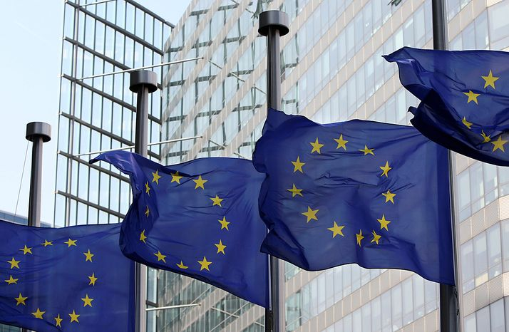 ** FILE ** European Union flags fly at half-mast in front of the European Commission headquarters in Brussels on Monday, April 12, 2010. (AP Photo/Yves Logghe)