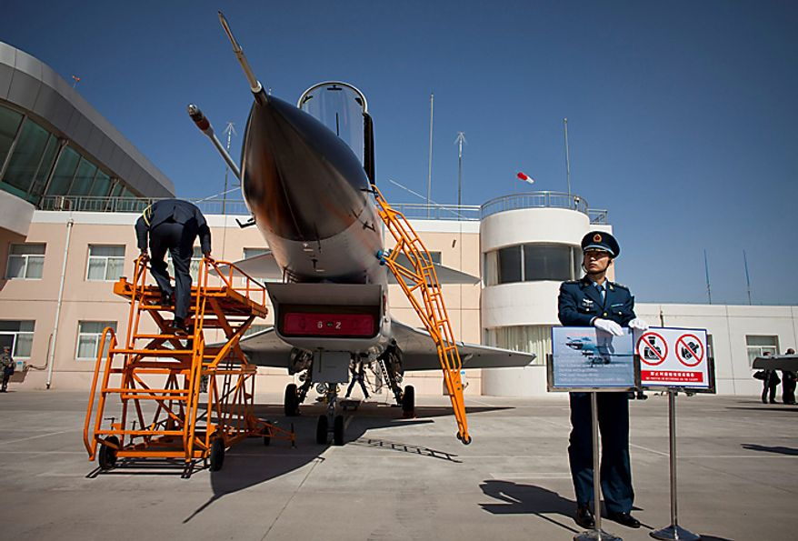 A Chinese People's Liberation Army Airforce officer, right, guards a J-10 fighter jet while a foreign military attache, left, climbs ladder to take a close look at the cockpit at a base of the PLA Airforce's 24th Division in Yangcun, Tianjin, China, Tuesday, April 13, 2010. The media, along with about 51 military attaches from embassies in Beijing, including the United States, Britain and Israel, witnessed a 15-minute demonstration by four pilots from the 24th Air Division in China's domestically developed J-10 fighters. (AP Photo/Alexander F. Yuan)