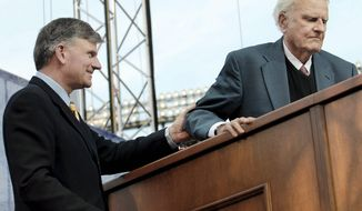 ** FILE ** The Rev. Franklin Graham (left) escorts his father, the Rev. Billy Graham, to the pulpit to deliver the final sermon at the Metro Maryland 2006 Franklin Graham Festival at Camden Yards in Baltimore. (The Washington Times)