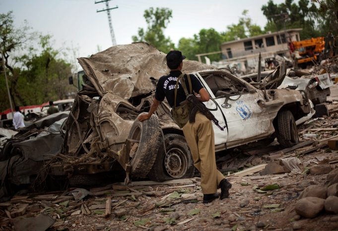 **FILE** A Pakistani police officer guards a U.N. car destroyed in June 2009 by suicide bomber at the Peshawar Pearl Continental Hotel. An increase in terrorist attacks in Pakistan and Afghanistan triggered a spike in the number of civilians killed or wounded in 2009, pushing South Asia past the Middle E