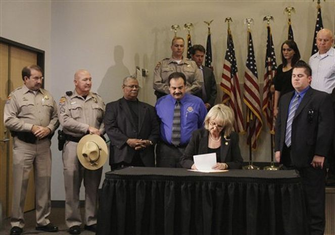 ** FILE ** With law enforcement supporters behind her, Arizona Gov. Jan Brewer signs immigration bill SB1070 into law on Friday, April 23, 2010, in Phoenix. The sweeping measure, major portions of which a federal court later blocked from implementation, would require local law enforcement to question people about their immigration status if there is reason to suspect they are in the country illegally. (AP Photo/Ross D. Franklin)