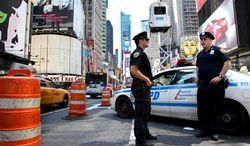 Two New York police officers patrol Times Square as a police lookout post towers in the background on Wednesday, May 5, 2010. (AP Photo/Craig Ruttle)