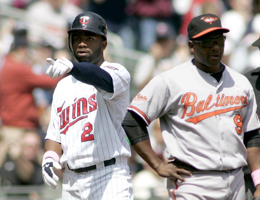 ASSOCIATED PRESS Minnesota Twin Denard Span, left, points to teammates after stealing third base as Baltimore Orioles Miguel Tejada stands next to him in the fourth inning of a baseball game Sunday, May 9, 2010, in Minneapolis.