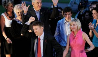 """TEA PARTY"" POWER: Republican U.S. Senate candidate Rand Paul (center) is accompanied by his wife, Kelley, his father and mother, Ron and Carl, and his son, William, as he arrives Tuesday evening for his victory party in Bowling Green, Ky. Mr. Paul trounced primary foe Trey Grayson, the Kentucky secretary of state."