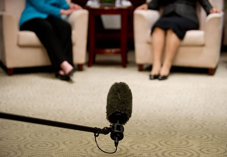A boom microphone captures the sound as Secretary of State Hillary Rodham Clinton (left) and Chinese State Councilor Liu Yandong take part in a meeting at the National Center for the Performing Arts in Beijing on Tuesday, May 25, 2010. (AP Photo/Saul Loeb, Pool)