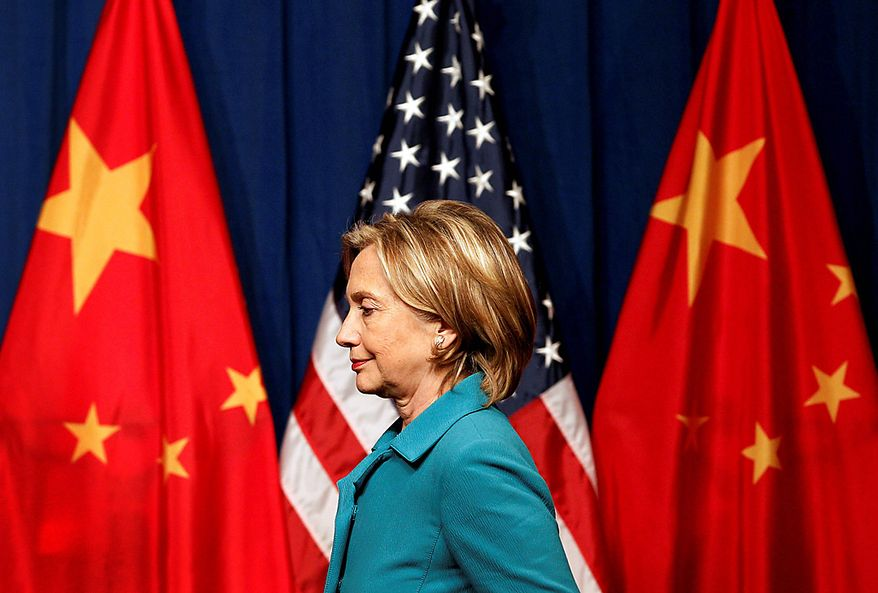 """Secretary of State Hillary Rodham Clinton walks past the U.S. and Chinese flags upon arrival at a press conference in Beijing on Tuesday, May 25, 2010. Mrs. Clinton stepped up pressure on China on Tuesday to back international action against North Korea for the sinking of a South Korean warship, calling peace and security on the Korean peninsula """"a shared responsibility"""" between Washington and Beijing. (AP Photo/Andy Wong)"""