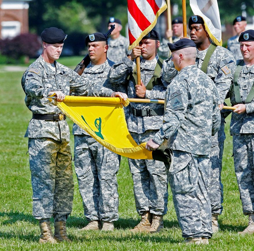 Maj. Gen. James Milano (left) prepares to case the Army Armor Center's flag at a change-of-command ceremony at Fort Knox, Ky. The center is moving to Fort Benning, Ga. (ASSOCIATED PRESS)