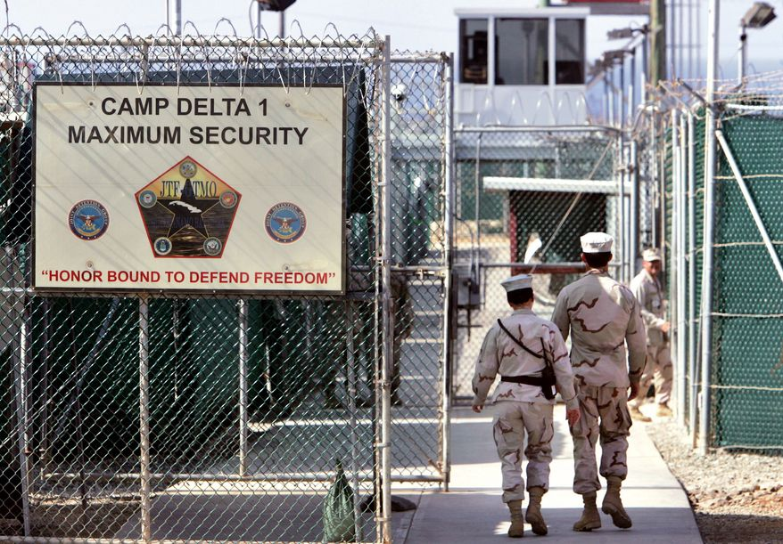 ** FILE ** In this Tuesday, June 27, 2006, photo reviewed by the U.S. Department of Defense, U.S. military guards walk within the Camp Delta detention center at the U.S. naval base at Guantanamo Bay, Cuba. (AP Photo/Brennan Linsley, File)