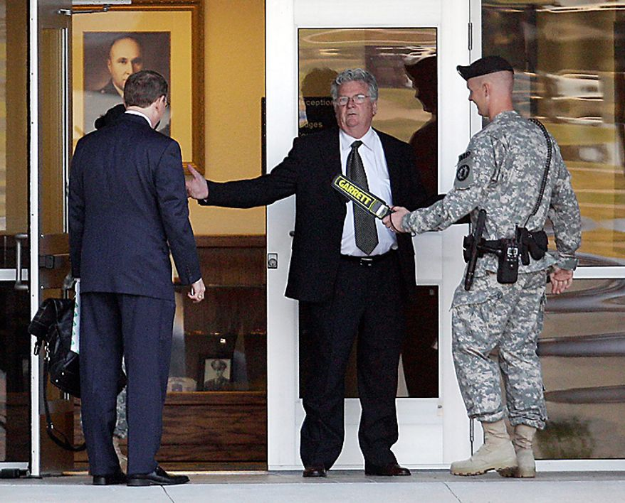 John Galligan (center), a defense attorney for Maj. Nidal Hasan, goes through a security check as he arrives for an Article 32 hearing on Tuesday, June 1, 2010, in Fort Hood, Texas. Major. Hasan, who is accused of opening fire at Fort Hood and killing 13 and wounding dozens more, was to make his first military courtroom appearance Tuesday as his attorney seeks to delay the case. An Article 32 hearing is similar to a civilian grand jury proceeding in which a judge hears witness testimony to determine whether the case should go to trial. No date has been set, but authorities have said the trial could be held as early as July 1. (AP Photo/Eric Gay)