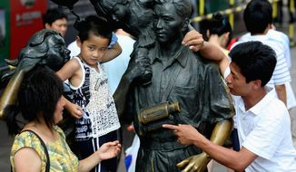 **FILE** A family stands next to a statue depicting a typical Chinese family with one child in Shanghai in 2008. (Associated Press)