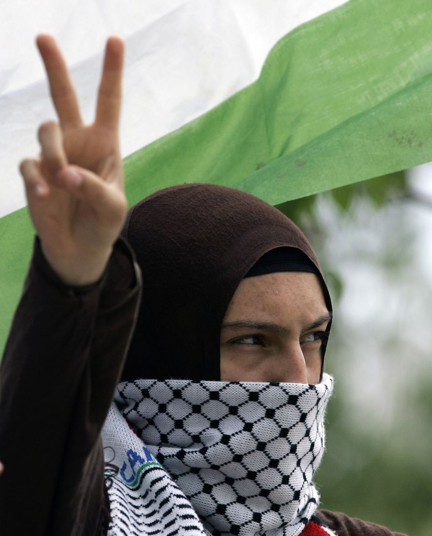 A pro-Palestinian woman flashes the V-sign as about a hundred people gather near the entrance to the residence of the Israeli ambassador to Turkey in Ankara, Turkey, on Wednesday, June 2, 2010, to protest Israel's commando raid on a flotilla carrying aid to the Gaza Strip. (AP Photo/Burhan Ozbilici)