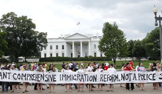 Demonstrators stand in front of the White House in Washington, Thursday, June 3, 2010, during a protests against the new Arizona immigration law. Arizona Gov. Jan Brewer met with President Barack Obama today to discuss state's new immigration law that the White House opposes. (AP Photo/Pablo Martinez Monsivais)