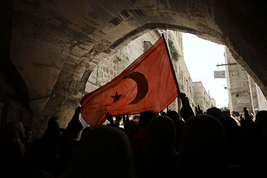 Palestinians hold up a Turkish flag as they take part in a demonstration against the Israeli naval commando raid on a flotilla attempting to break the blockade on Gaza, after prayers in Jerusalem's Old City, Friday, June 4, 2010. Israel is bracing for another showdown at sea with pro-Palestinian activists determined to breach Israel's Gaza Strip blockade. A small aid ship, the Rachel Corrie, is making its way toward Gaza's shores just days after Israeli naval commandos took over six other Gaza-bound ships in a raid that left eight Turks and an American of Turkish descent dead. (AP Photo/Tara Todras-Whitehill)
