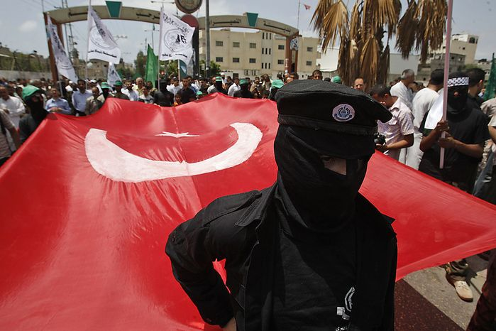 Masked Palestinian Hamas members hold up a Turkish flag as they takes part in a demonstration against the Israeli naval commando raid on a flotilla attempting to break the blockade on Gaza, after Friday prayer at Nuseirat refugee camp in central Gaza Strip, Friday, June 4, 2010. Israel is bracing for another showdown at sea with a ship determined to breach Israel's Gaza Strip blockade. (AP Photo/Hatem Moussa)