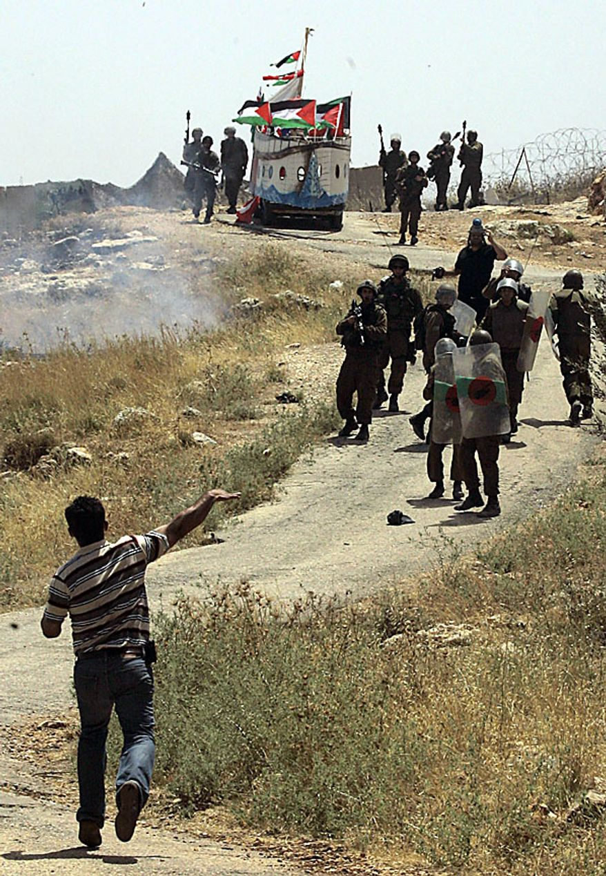 A Palestinian demonstrator hurls a stone towards Israeli forces after they stopped a vehicle, top, decorated in the shape of a ship, depicting one of the ships taking part in the recent humanitarian aid flotilla that tried to get to Gaza, during a protest against Israel's separation barrier, in the outskirts of the West Bank village of Bilin, near the city of Ramallah, Friday, June 4, 2010. Tensions are high in the aftermath of an Israeli naval raid targeting the aid flotilla to Gaza that killed nine pro-Palestinian activists, mostly Turks, in the ensuing clash. (AP Photo/Nasser Ishtayeh)