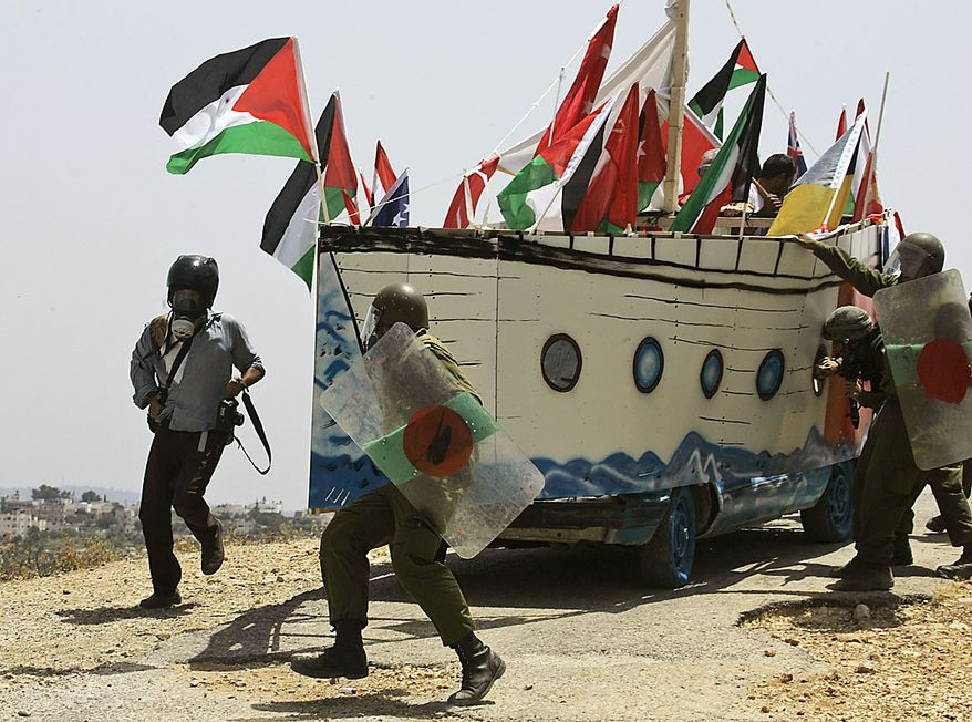 A photojournalist (left) runs Friday June 4, 2010, as Israeli soldiers try to stop a vehicle decorated in a shape of a ship by Palestinian, Israeli and international protesters. The vehicle depicted one of the ships of the humanitarian flotilla that tried to get to Gaza, during a protest against Israel's separation barrier, in the outskirts of the West Bank village of Bilin, near the city of Ramallah. Tensions are high in the aftermath of an Israeli naval raid targeting the aid flotilla to Gaza that killed nine pro-Palestinian activists, mostly Turks, in the ensuing clash. (Associated Press)