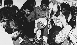 Mother Teresa comforts a young victim of the Bhopal, India, gas-leak disaster on Dec. 11, 1984. (AP Photo) ** FILE **