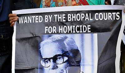 "An elderly survivor holds a poster of Warren Anderson, the head of Union Carbide Corp. at the time of the gas leak, as she waits for the verdict in the premises of Bhopal court in Bhopal, India, on June 7, 2010. The court convicted seven former senior employees of Union Carbide's Indian subsidiary of ""death by negligence"" for their roles in the Bhopal gas tragedy that left an estimated 15,000 people dead more than a quarter century ago in the world's worst industrial disaster. (Associated Press)"