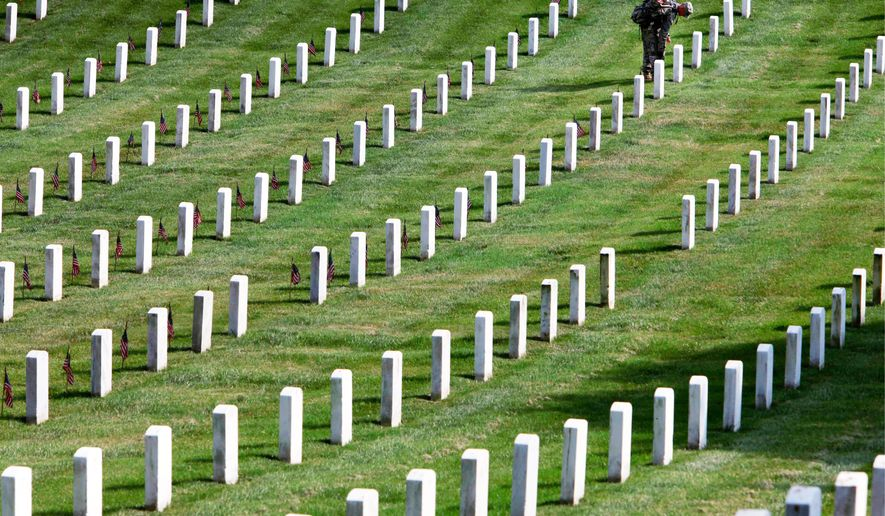 """Army Spc. Matthew Burt, 25, of Titusville, Penn., with the 3rd U.S. Infantry Regiment, known as """"the Old Guard,"""" places flags on the graves at Arlington National Cemetery in Arlington, Va., on May 27. At least 211 remains were identified as potentially mislabeled or misplaced. (Associated Press photographers)"""