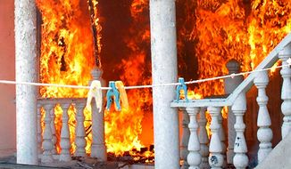 An Uzbek's home burns after being torched by Kyrgyz men in Jalal-Abad, Kyrgyzstan, on Sunday. Thousands of Kyrgyz men brandishing sticks, metal bars and hunting rifles burned Uzbeks' property in the Central Asian nation as frightened police stayed away. (Associated Press)