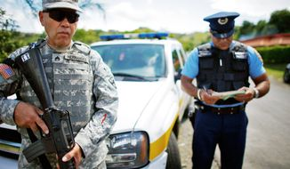 Puerto Rican U.S. Army National Guard Staff Sgt. Raul Hernandez (left) stays alert during a joint patrol with a police officer in Orocovis, Puerto Rico. The U.S. Caribbean territory's governor is calling up as many as 1,000 National Guard soldiers this year to quell crime in Puerto Rico. (Associated Press)